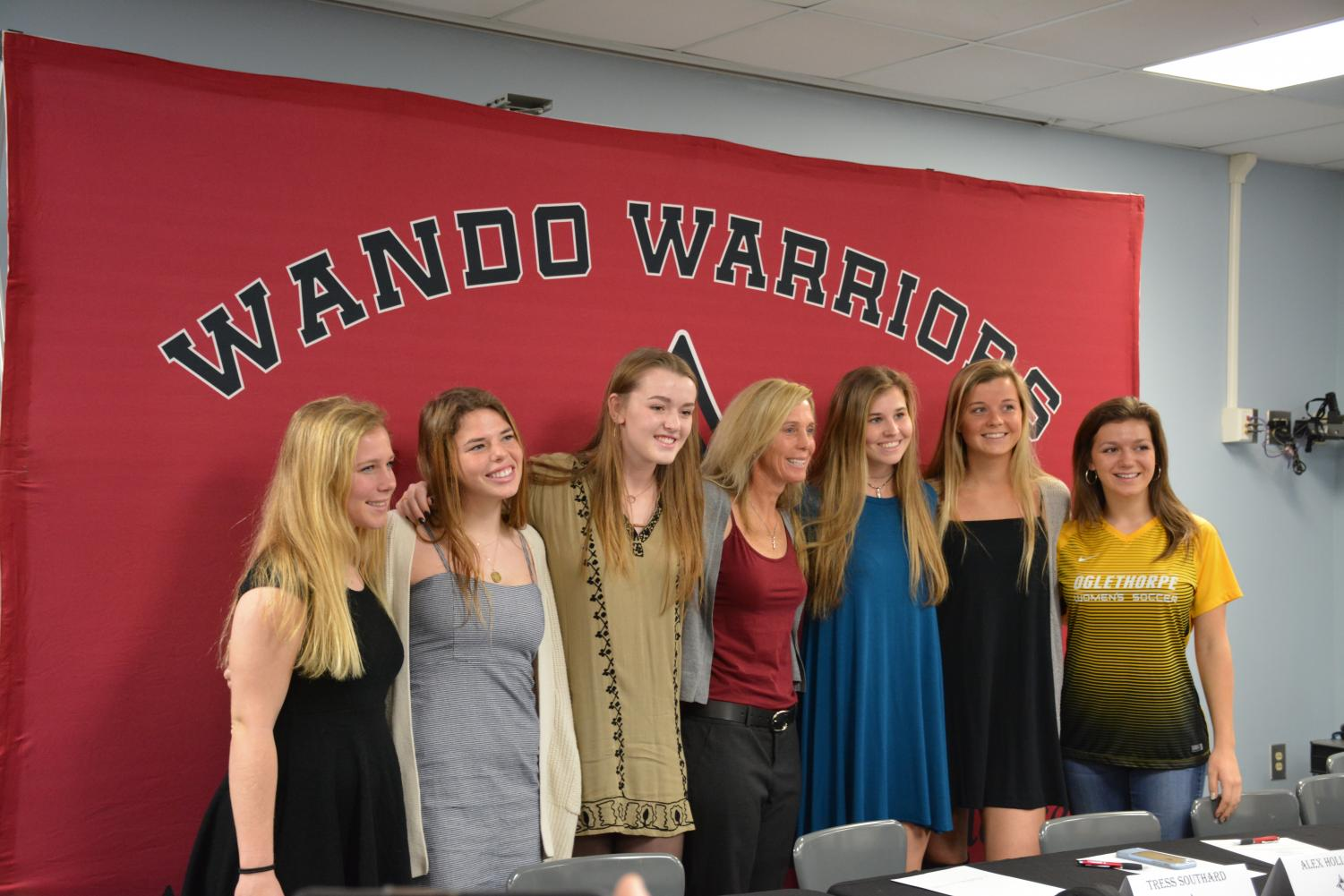 Wando+Girl%27s+Soccer+signees+stand+with+their+Wando+coach+Shannon+Champ.