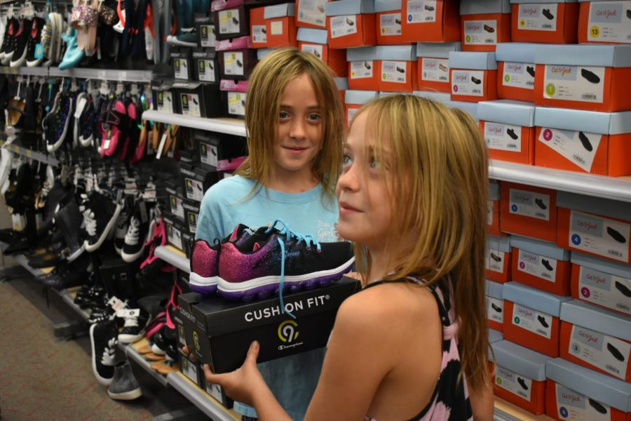 Two girls look through shoes while at the Happy Feet event.