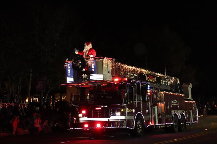 Santa Claus travels down Coleman Blvd perched on top of a firetruck.