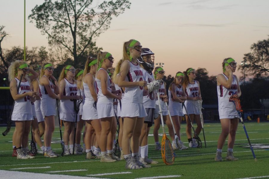 The girls' lacrosse team wears green to support their coach on her road to recovery.