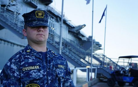 Sam Overman stands next to a naval ship in full uniform.