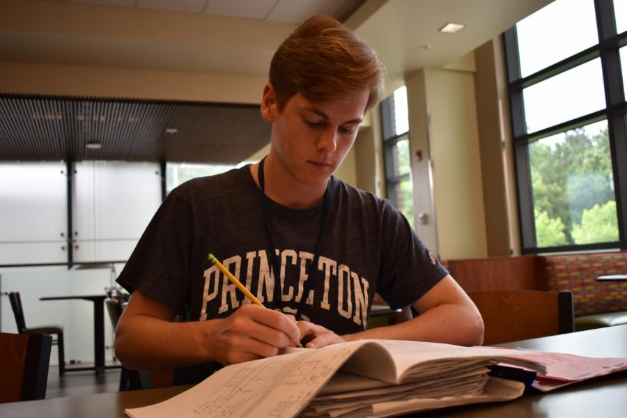 Jack+Johnson+prepares+for+his+AP+exams+while+sporting+a+shirt+representing+his+future+college.+
