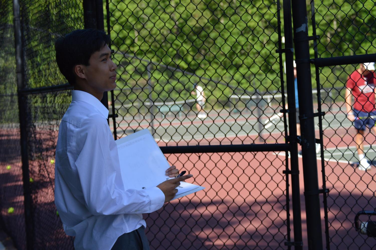 Andrew Nguyen watches over the tennis team as they perform.
