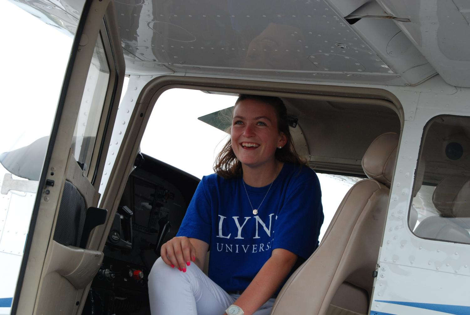 Addison Terry sits in the cop pit of a plane in preparation for a flight.