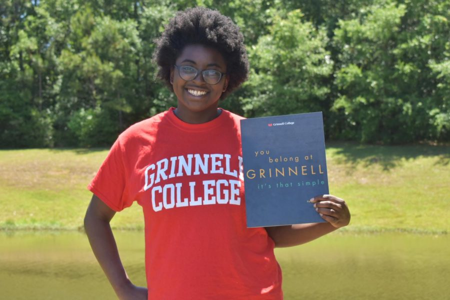 Sharena+Brown+proudly+displays+her+acceptance+letter+and+future+college+shirt.+