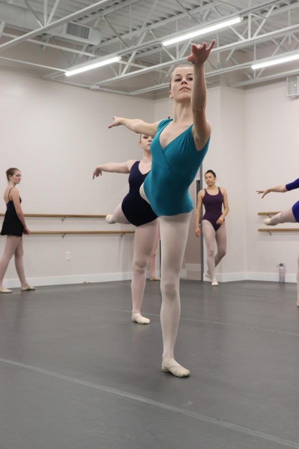 Hathaway and other dancers hold arabesques while rehearsing for