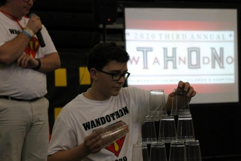 Freshmen Connor Bosse does a miniature cup building challenge to raise money for Shawn Jenkins.