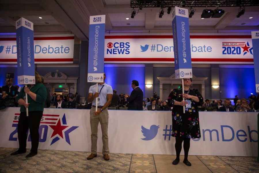 Debate staffers holding signs to help press locate campaign representatives after the debate.