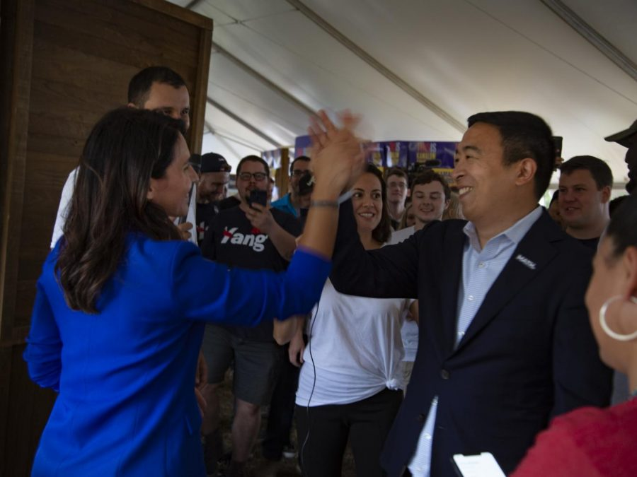 Presidential candidates Andrew Yang and Tulsi Gabbard high five next to Tulsi 2020 campaign booth.