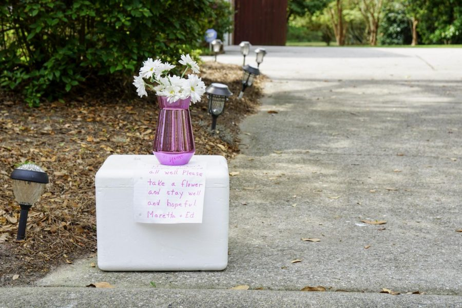 """A vase of flowers with a note reading """"Please take a flower and stay well and hopeful"""" sits on a cooler outside Maretta and Ed McKenna's house. Maretta has set up interactives on her driveway since March 30, including chalk passerbys could draw with."""