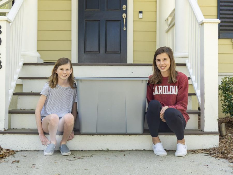 Eliza and Caroline Bierman sit next to a donation bin on March 2. They worked with their mom to bag snacks and medical supplies that were donated to hospitals in the Charleston area.
