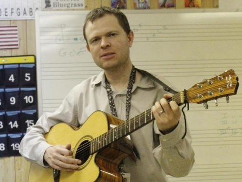 Derek Deakins plays his guitar in his trailer classroom at Wando. At the school, he teaches music theory and guitar, and also conducts the Wando High School Orchestras.