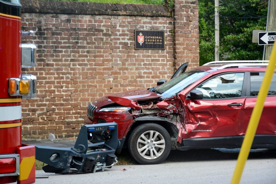 A wrecked car sits off the shoulder of a downtown road, after colliding with a National Guard truck.