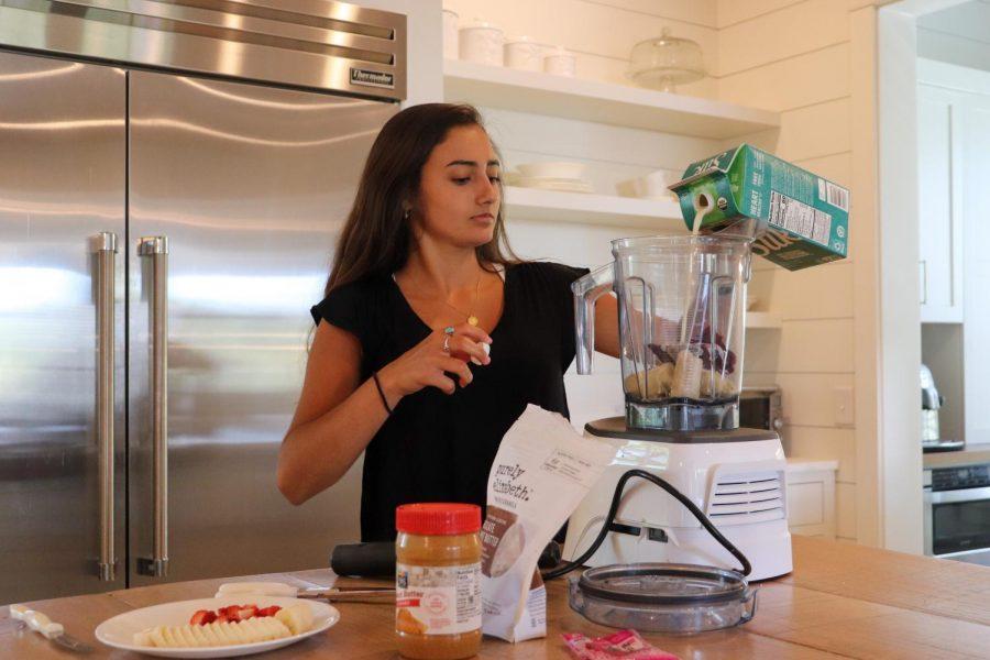 Ava Elliot pouts Silk milk into her blender.