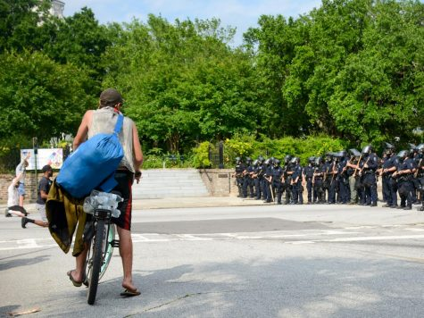 A bicycling protester rides by with waters to aid people affected by tear gas and dehydration.