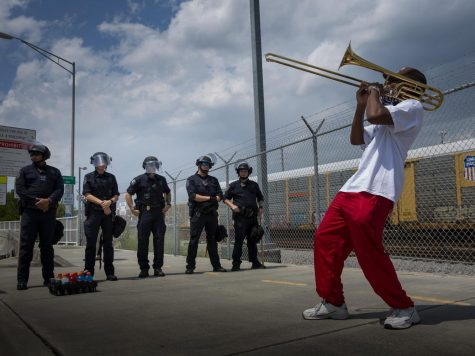Protester Marcus McDonald playing the trombone for officers at a police checkpoint to the Ravenel bridge. The East Bay bridge entrance had been shut down to prevent a protest from occurring on the bridge as originally planned.