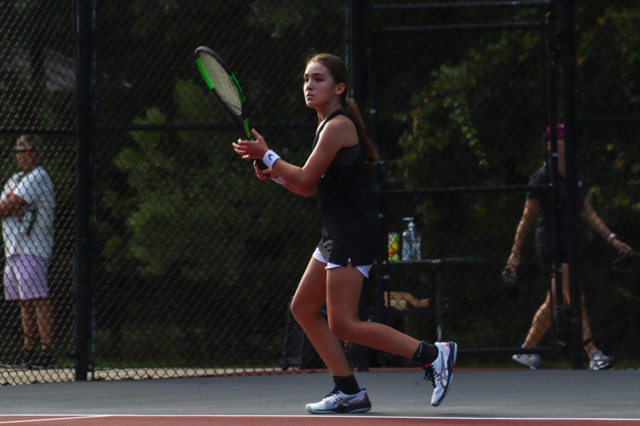 Jenna Zimmerman, 8, in an open stance along the baseline, waiting for the opponent to serve the ball.