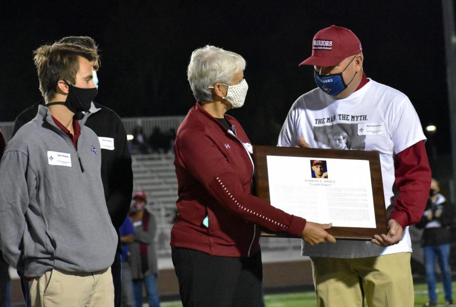 During halftime, a tribute to former athletic director Bob Hayes was played on the main screen of the stadium. His wife and son are pictured accepting a plaque in his honor.