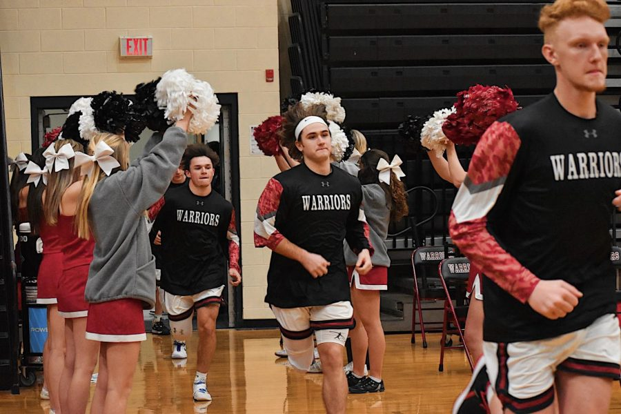 (Right to left) Seniors David Holmes and Ian Coste, and Junior Will Hill, run out from the locker rooms into the gym at the beginning of the game.