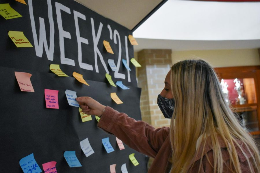 Junior Alli Ryan pulls a sticky note off of the 'Take What You Need' board in the rotunda.