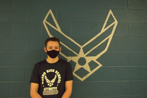 Senior Zane Gillies posing in front of the Air Force service symbol in his JROTC uniform.
