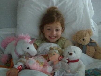 Emory sits in her bed as a young child surrounded by her stuffed animals.