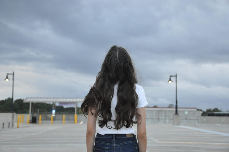 Scarlett Lewis standing in the middle of a parking lot looking at the sky.