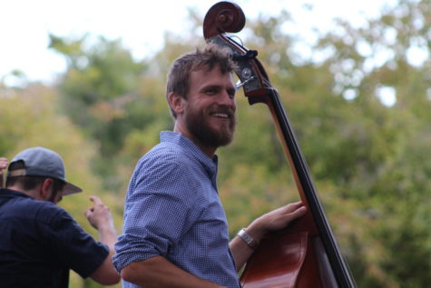 Anthony Del Porto from The Pluff Mud String Band smiles at the crowd while playing his bass.